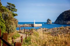 Footpath along the sea on the island of Jeju South Korea beautiful seascape. View of the lighthouse. Travel to Asia royalty free stock photos
