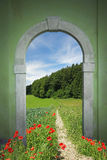 Footpath through arched door, spring landscape Royalty Free Stock Photography