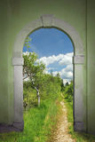 Footpath through arched door into wild bogland Stock Image