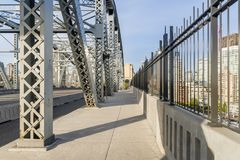 Footpath on a bridge with metal supports in a modern city Royalty Free Stock Photo
