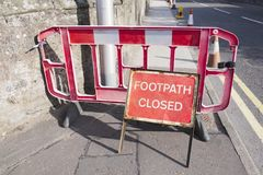 Footpath closed sign for pedestrian safety from road construction on busy street. Uk royalty free stock images