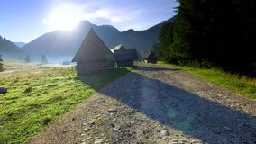 Footpath between cottages in the valley Chocholowska at sunrise, Tatra Mountains stock video