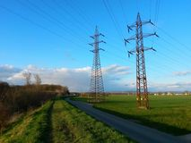 Footpath on creek dike along asphalt road, with view of masts, field and meadow. Image stock photo