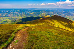 Footpath down the hill through mountain ridge. Summer mountain landscape. footpath down the hill through mountain ridge to valley. huge boulders on grassy slope Royalty Free Stock Images