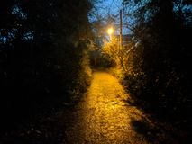 Footpath at dusk. A local footpath in Southern England, dimly lit with the remains of the day`s sun and the warm glow of old sodium street lamps Royalty Free Stock Images