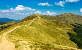 Footpath through the grassy hills of mountains. Beautiful summer scenery in fine weather with some clouds on a blue sky Stock Image