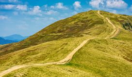 Footpath through the grassy hills of mountains. Beautiful summer scenery in fine weather with some clouds on a blue sky Stock Photo