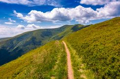 Footpath through grassy mountain ridge. Beautiful summer landscape under gorgeous sky with clouds Royalty Free Stock Photography