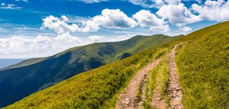 Footpath through grassy mountain ridge. Footpath through panorama of grassy mountain ridge. beautiful summer landscape under gorgeous sky with clouds Stock Photography
