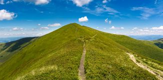 Footpath through grassy peak of mountain ridge. Gorgeous panorama of summer landscape with fine weather and blue sky with some clouds. hiking destination Royalty Free Stock Images