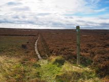 Footpath with marker post leading across moors. Footpath with marker post leading across Brow Moor in the North York Moors National Park, Yorkshire, UK Stock Photo