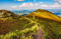 Footpath through a meadow on mountain ridge. Winding footpath through meadows with rocks on the hillside of Carpathian mountain range. Beautiful summer landscape Stock Photo