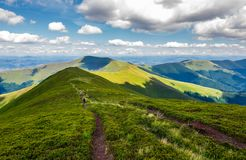 Footpath through mountain ridge in summer. Group of tourists following the path. lovely landscape and travel concept Royalty Free Stock Photos