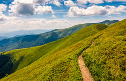 Footpath through the mountain ridge. Summer mountain landscape. footpath uphill through the ridge to the peak. beautiful Carpathian nature scene Stock Image