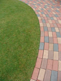 Footpath next to grass. Curved footpath next to the grass stock photo
