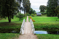 Footpath in old park with white wooden bridge royalty free stock photography
