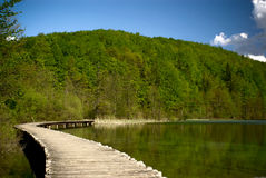 Footpath over clear mountain lake in national park Royalty Free Stock Photography