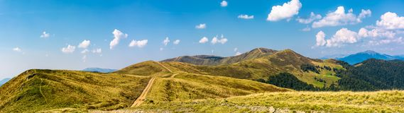 Footpath through rolling hills of mountain ridge. Gorgeous panorama of early autumn landscape with fine weather and blue sky with some clouds. hiking direction Royalty Free Stock Photos
