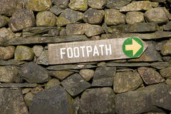 Footpath sign. With a green arrow pointing right on a stonewall Royalty Free Stock Photography