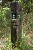 Footpath sign with arrow. On small lichen covered pole showing walk direction Stock Photo