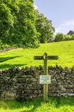 Footpath sign on a sloping green field Stock Images
