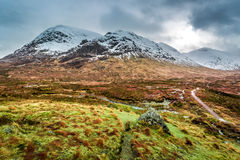 Footpath between snowy mountains Stock Images