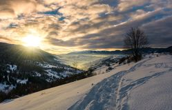 Footpath through snowy rural hillside. Gorgeous sunrise in mountainous winter countryside Royalty Free Stock Image