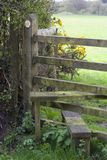 Footpath and stile, UK. A leathy path leading to a wooden fence stile. Yellow arrow marking the route stock image