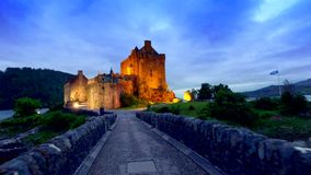 Footpath to the beautiful illuminated Eilean Donan Castle at sunset, Scotland stock video