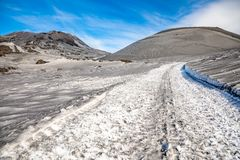 Footpath to Etna Volcano with smoke in winter, volcano landscape, Sicily island, Italy stock image