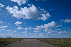Footpath to heaven. Footpath towards the beach and white clouds with blue sky Stock Photography