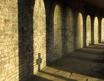Footpath to religion. Shadow of a cross on the wall of a cemetery Royalty Free Stock Images