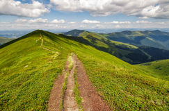 Footpath on top of a mountain ridge in summer. Footpath on top of a mountain ridge with grassy slippery slopes. gorgeous scenery in wonderful summer weather with Stock Photography