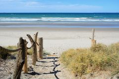 A sandy steep footpath leading to the sea; wooden decorations on one side of the path; beautiful sunny day and bright blue sea royalty free stock photography