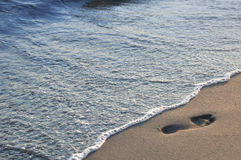Footprint on beach. Footprint on the sandy beach and sea wave Stock Photo