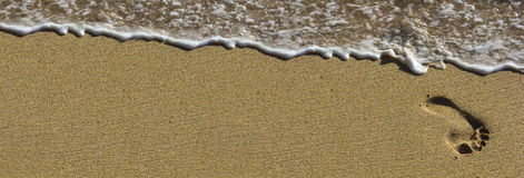 Footprint at beach with waves stock photo