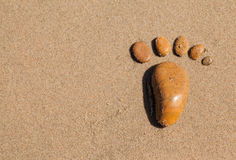 The footprint made up of stones in the sand Royalty Free Stock Photos
