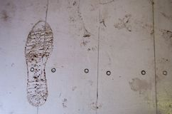 Footprint of a man made of mud on a white wooden board viewed from above, background on the footprint royalty free stock image
