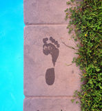 Footprint. Picture of a wet footprint next to an outdoor pool Royalty Free Stock Photos