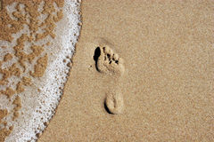 Footprint on sand. And sea foam Royalty Free Stock Photos