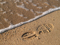 Footprint in the sand. Shoe-print in wet sand with wave stock photography