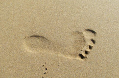 Footprint on sand. Beach near the sea. Beautiful drawings on the yellow smooth sand. Leisure on the beach, romantic love Royalty Free Stock Images
