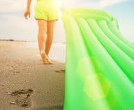 Footprint on sand - boy with swimming mattress walks on the sand Stock Photo