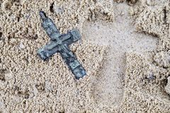 Footprint in the sand from a large cross lying next to a small