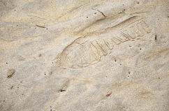 Footprint of the shoe in the sand. Footprint soles of sports shoes in the wet sand of the beach Royalty Free Stock Photo