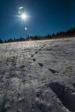 Footprint on snow  and blue sky with Sun flare Stock Photos