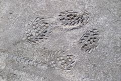 The footprint of a sports shoe imprinted in concrete. An imprint stock photography
