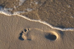 Footprint and wave on beach. Royalty Free Stock Image