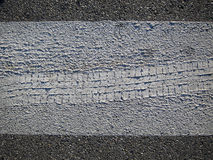 Footprint wheel in the asphalt Stock Images