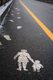 Footprints. Pictograph of a mother and child on the street together with footprints leading their safe way royalty free stock photo